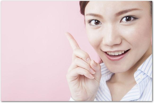 人差し指を立てている笑顔の女性の様子