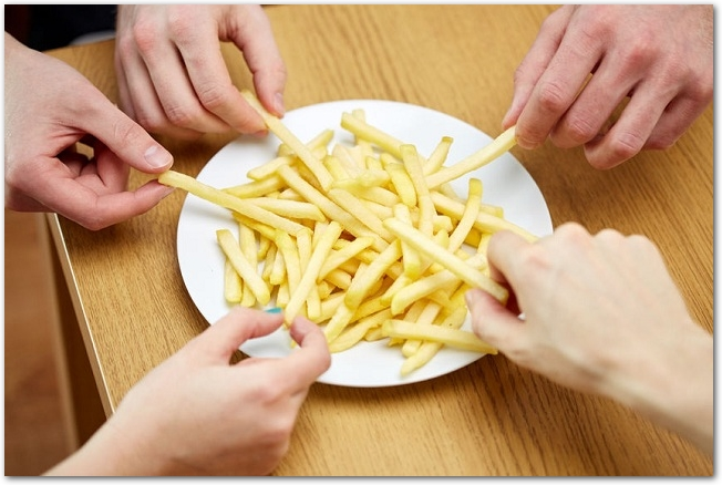 フライドポテトのお皿に五人が手を伸ばしている様子