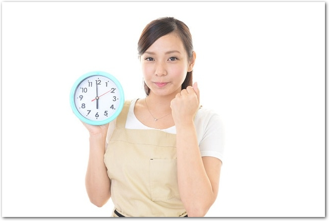 時計を持ってガッツポーズをするエプロン姿の女性