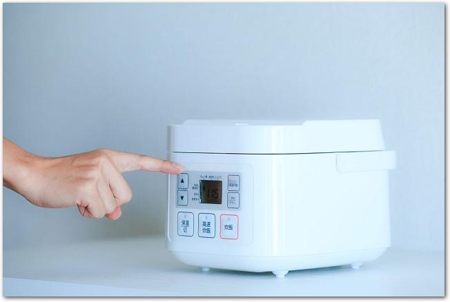 炊飯器のスイッチを押そうとしている手元の様子