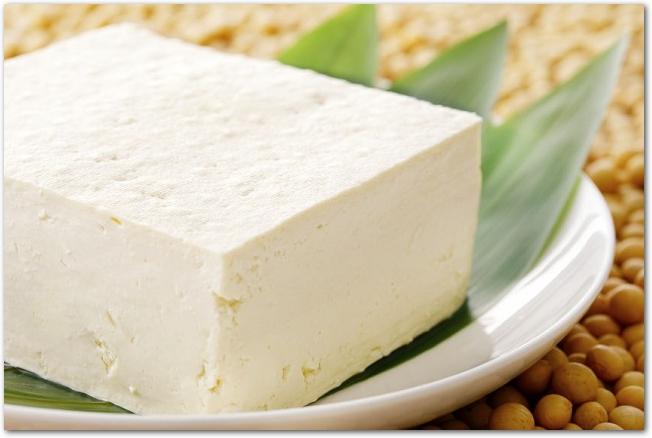 笹の葉が敷かれた白皿に乗っている豆腐
