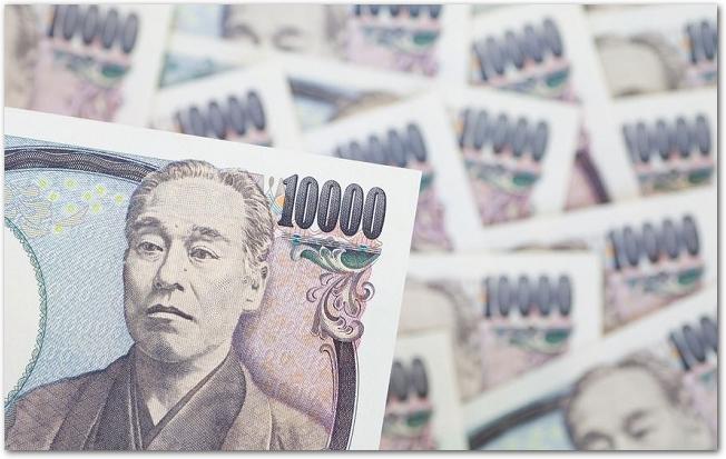 たくさんの一万円札のうち手前の一枚にピントがあっている様子