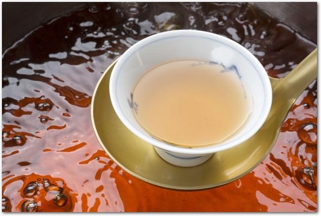 だし汁の鍋の上にあるおたまに乗った器にだし汁が入っている様子
