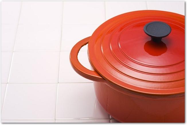 白いタイルの上に置かれたオレンジ色のホーロー鍋