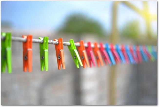 洗濯物を干すロープにカラフルな洗濯バサミがたくさんついている様子