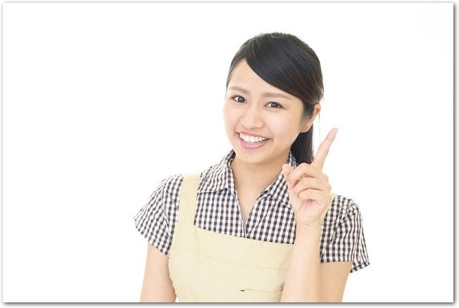 指を指すエプロン姿の笑顔の女性の様子