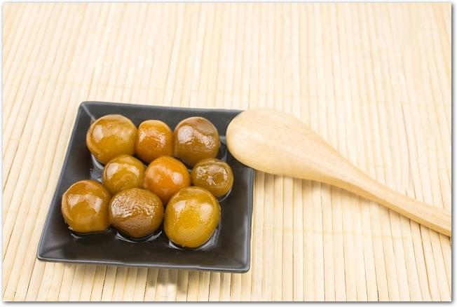 角皿に入った金柑の甘露煮と木のスプーン