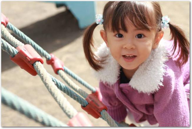 アスレチックで遊ぶ3歳の女の子の笑顔