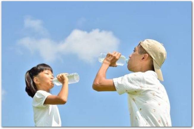 青空を背景に水を飲む父親と娘の様子