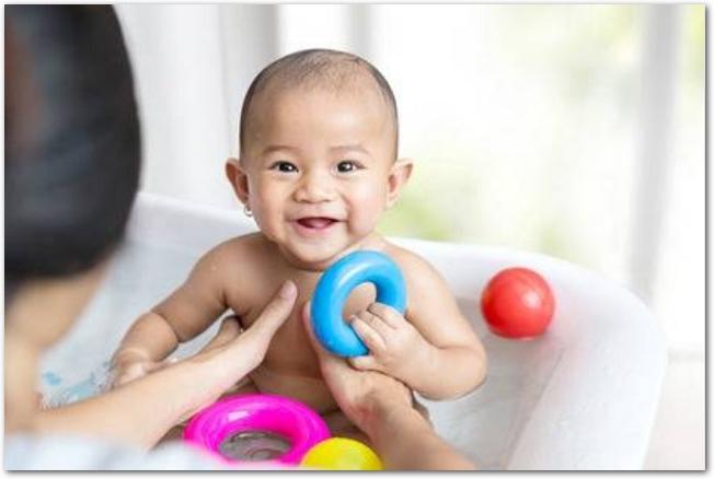 おもちゃを手にお風呂で遊ぶ笑顔の赤ちゃん