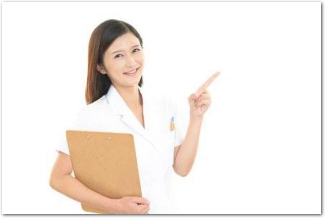 クリップボードを持って指を指す女性栄養士の様子