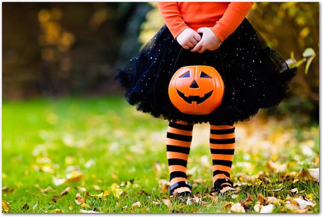 かぼちゃの飾りを持つハロウィンカラーの服を着た女の子